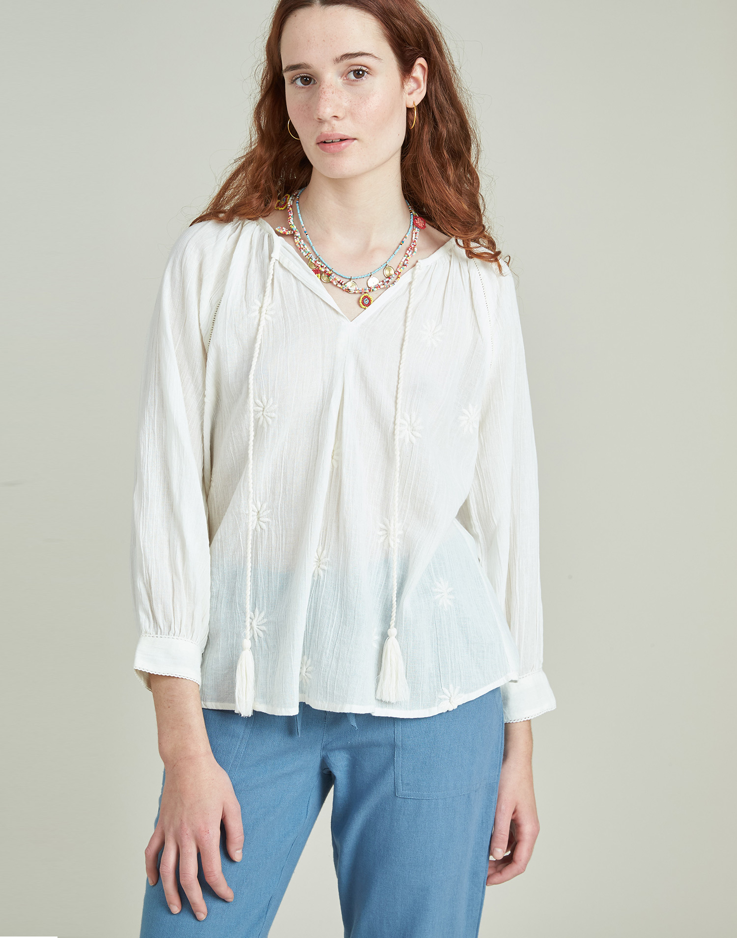Embroidered blouse with pompoms